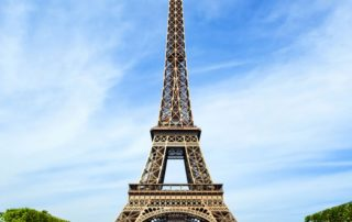 Photo of the Eiffel Tower in France with a blue sky background.