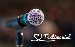"Photo of turquoise and black microphone with the word ""testimony"" written in white letters."