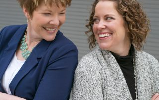BF Bookkeeping Owners Meghan and Stacy Looking at each other and smiling