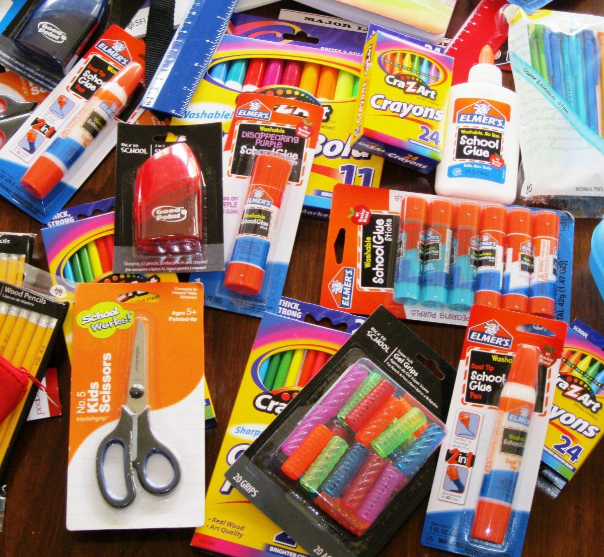 A table full of school supplies - glue sticks, scissors, pencils, etc.