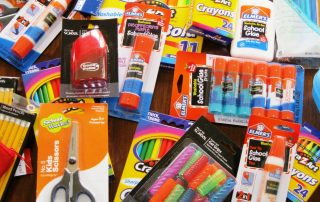 A table full of school supplies - glue sticks, scissors, pencils, etc.