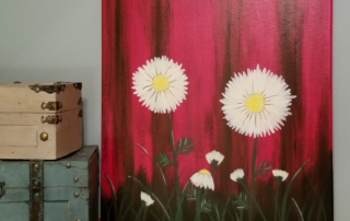 Canvas painting of daisies growing next to a red barn wall.
