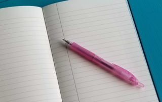 Photo of pink pen and a blank page in notebook.