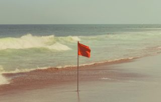 Picture of red flag flying on a rocky shore line while the sun is rising in the background.
