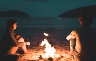Photo of campfire on the beach at sunset.