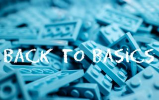 """Photo of turquoise legos and white letters spelling out """"back to basics""""."""