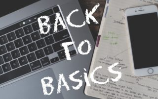 """Photo of cell phone and laptop on wooden desk top with the words """"Back to Basics""""."""