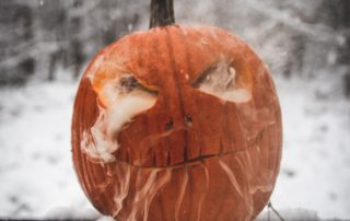 Picture of a jack-o-lantern in the snow on a porch railing.