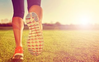Photo of a person's feet running on grassy field with sun high in the sky.